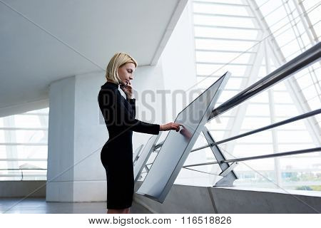 Elegant businesswoman consulting via cell telephone about report on modern interactive display