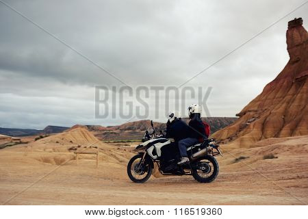 Two bikers in helmets riding on a motorcycle in extreme conditions in the mountains