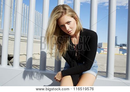 Young attractive hipster girl posing while sitting outdoors in sunny summer day
