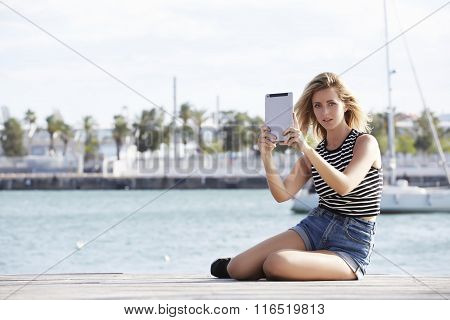 Hipster girl posing while taking photo with portable touch pad