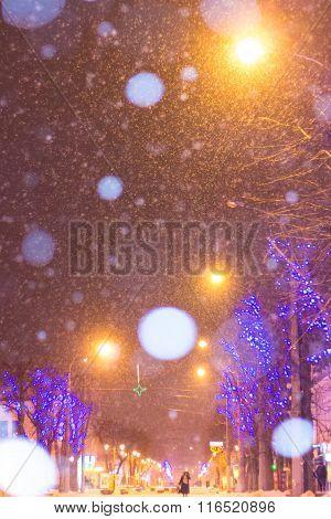 Christmas Night City Street Snowfall, Focus On Foreground Lamp