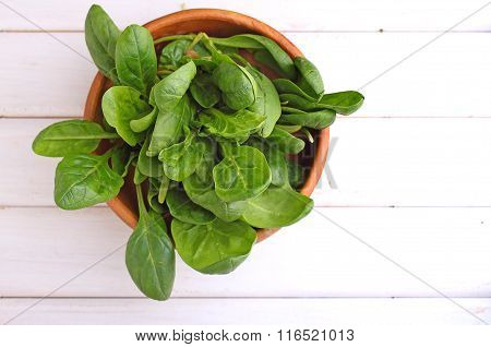 Green Spinach Leaves On White And Black Vintage Background