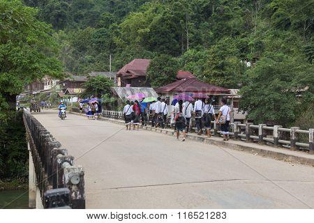 Students Walking Back From School On A Bridge.