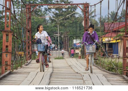 Young Unidentified Girl Cycling Back From School On A Wooden Bridge.