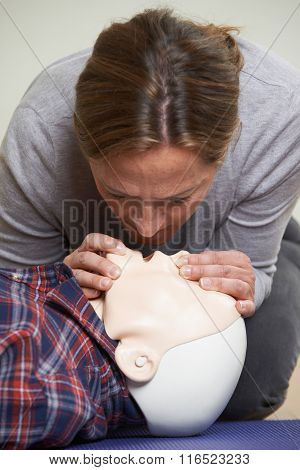 Woman In First Aid Class Performing Mouth To Mouth Resuscitation On Dummy