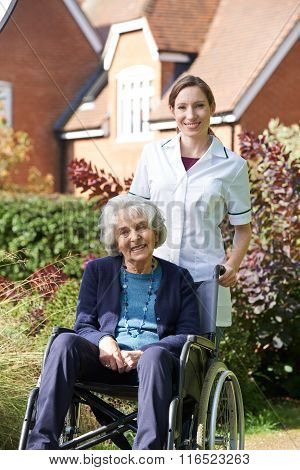 Portrait Of Carer Pushing Senior Woman In Wheelchair
