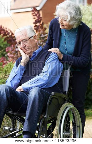 Depressed Senior Man In Wheelchair Being Pushed By Wife