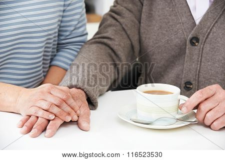 Close Up Of Woman Sharing Cup Of Tea With Elderly Parent