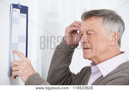 Confused Senior Man With Dementia Looking At Wall Calendar