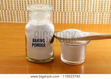 baking powder in glass bottle and wooden spoon