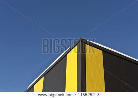 Snow On The Roof Of Yellow And Brown Warehouse.