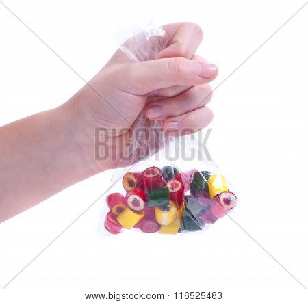 In A Hand Holding A Transparent Bag With Lots Of Multi-colored Caramel Sweets With Cool Designs