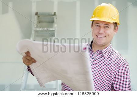 Smiling Contractor Holding Blueprints Inside Home Construction Site.