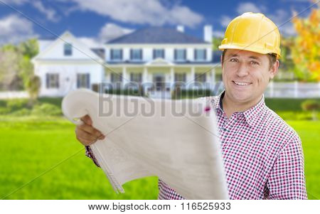 Smiling Contractor Holding Blueprints In Front of  Beautiful Custom Home.
