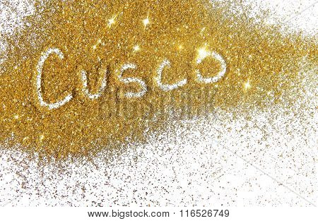 Blurry inscription Cusco on golden glitter sparkles on white background