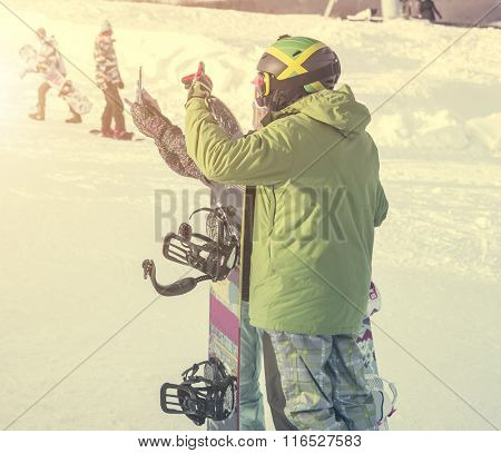 peolpe in ski suits with snowboards taking photo on a hill