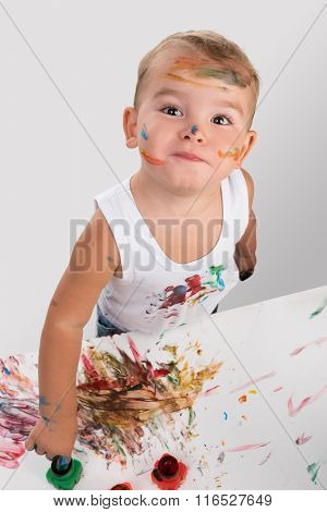 little boy painting with fingers
