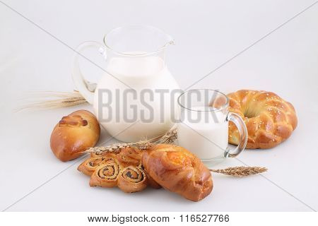 Milk In A Transparent Jug And Buns On A White Background