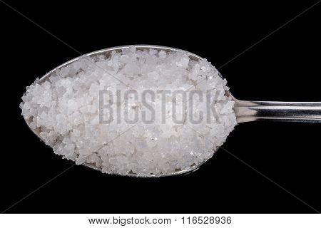 Sea salt in a large spoon. On a black background.