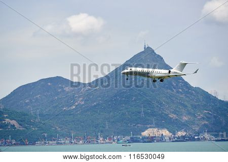 HONG KONG - JUNE 04, 2015: Bombardier Global Express aircraft landing at Hong Kong airport. The Bombardier Global Express is a large cabin, ultra long range business jet