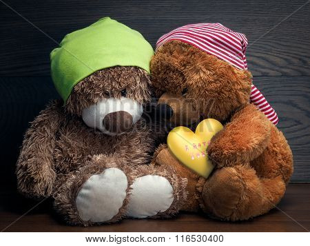 Two cute teddy bear and a heart of gold with the inscription
