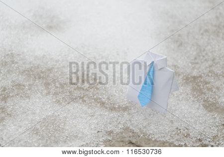 White business origami suit with blue tie on snow ground