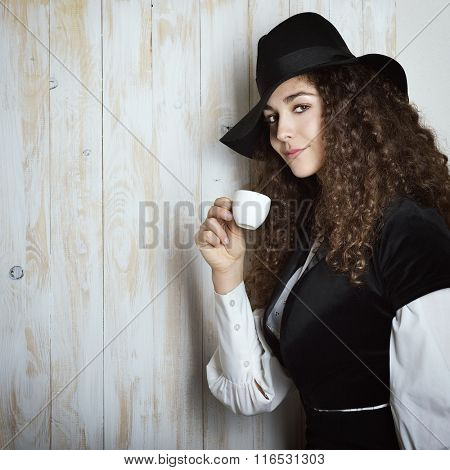 Young attractive woman with rich long curly brown hair in retro dress and hat drinking coffee. Vintage stylization of lady with cup of coffee smelling delicate aroma of beverage.