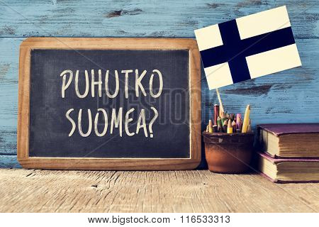 a chalkboard with the question puhutko suomea, do you speak Finnish? written in Finnish, a pot with pencils, some books and the flag of Finland, on a wooden desk