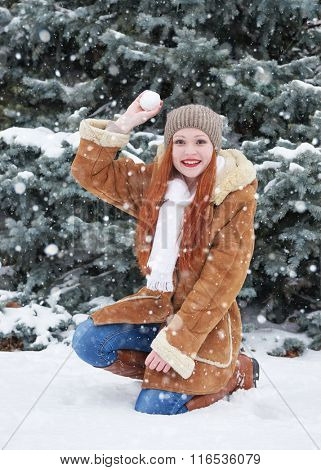 Girl play snowballs in winter park at day. Snowy fir trees. Redhead woman full length.