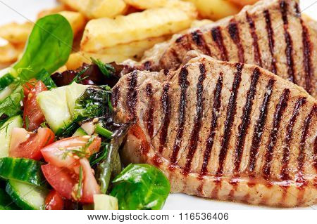 Grilled pork meat  with fried potatoes and vegetables