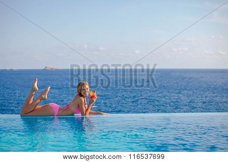 summer woman drinking cocktail in Mallorca in infinity pool