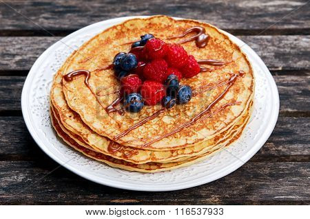 Fresh golden pancakes with raspberries, blueberries and chocolate.