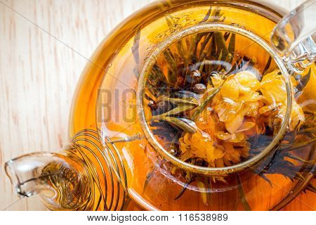 Exotic Green Tea Flowers In Glass Teapot, Top Close Up View