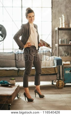 Young Smiling Businesswoman Holding Magazine In Loft Style Room