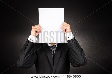 Businessman is Hiding Behind a White Blank Paper