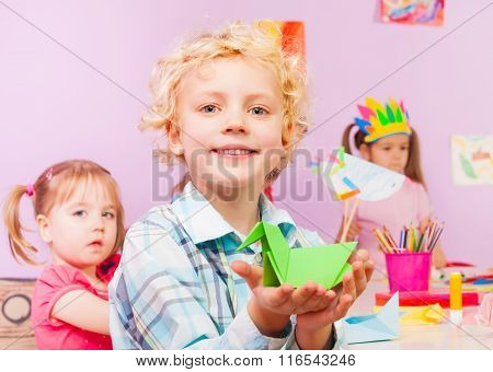 Handsome blond boy shows origami in classroom