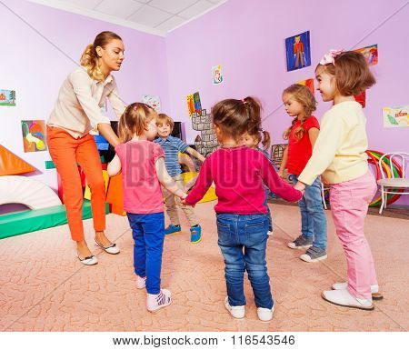 Little children and teacher roundelay on lesson