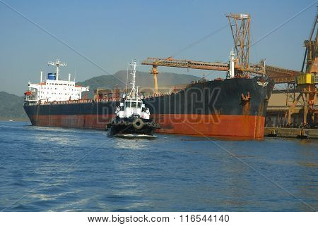 Grain Ship Docked And Tugboat