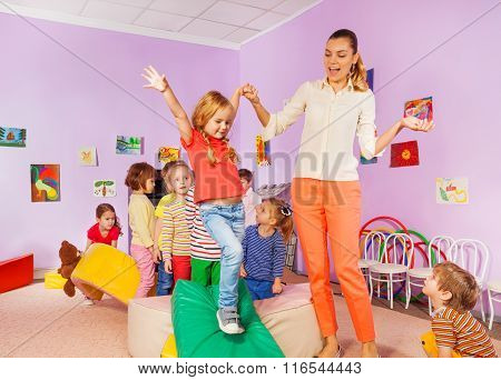 Kids run, climb around soft block in active class