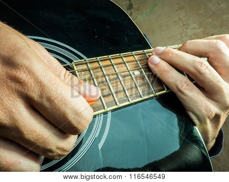 Closeup photo of an acoustic guitar played by a man.
