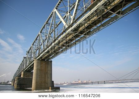 Railway Bridge Over The River Frozen Winter. Photographed From Below Cityscape In Winter.