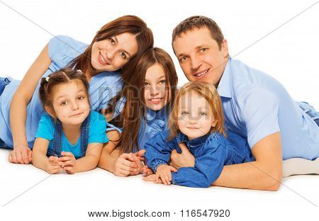 Family of parents and 3 girls lying at the floor