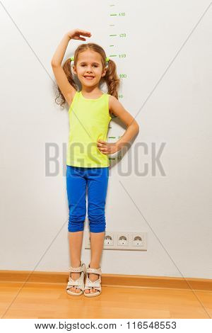 Cute girl checking height on wall with hand