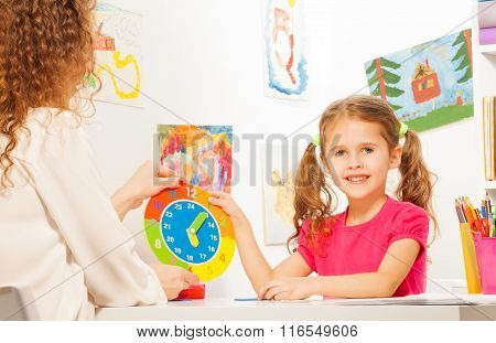 Girl studying time with the cardboard clock model