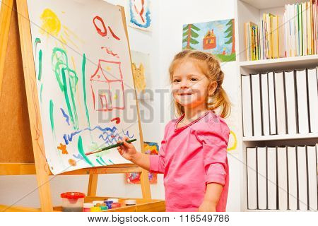 Cute girl is drawing using a brush at easel
