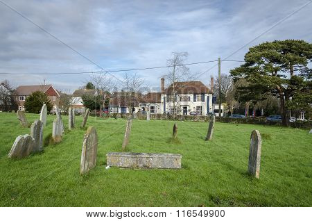 Headstones In A Churchyard With The Village Pub In The Background
