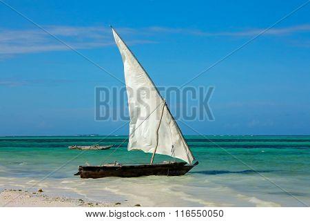 Wooden sailboat (dhow) on a tropical beach of Zanzibar island
