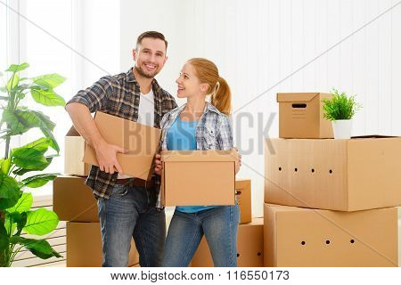 Moving To A New Apartment. Happy Family Couple And Cardboard Boxes.