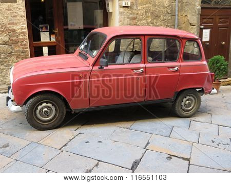 VOLTERRA ITALY - CIRCA DECEMBER 2014: A red Renault 4 parked in the old city centre.