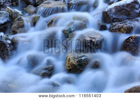 small waterfall on mountain river at winter time